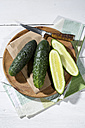 Sliced and whole cucumbers (Cucumis sativus) with knife on chopping board - MAEF007825