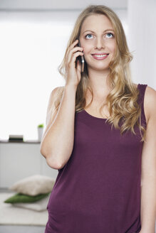 Portrait of young woman leaning against wall telephoning with smartphone - PDF000638