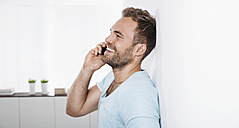 Portrait of young man leaning against wall telephoning with smartphone - PDF000654