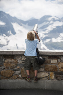 Austria, Grossglockner, Young boy watching through a binocular - PAF000397
