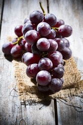 Red grapes on jute and wooden table - MAEF007859
