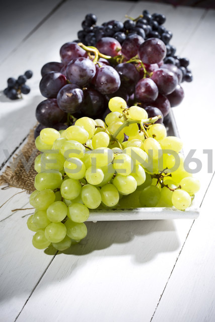 Bowl of different seedless white and blue grapes on jute and wooden table - MAEF007864 - Roman Märzinger/Westend61