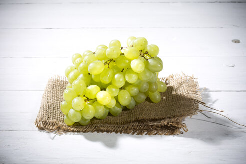 Seedless white grapes on jute and white wooden table - MAEF007865