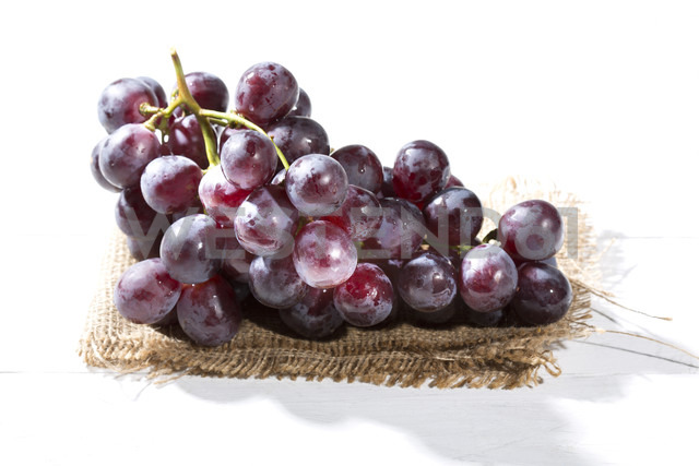 Red grapes on jute and white wooden table - MAEF007866