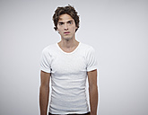 Portrait of serious looking man wearing white t-hirt in front of white background - RH000278