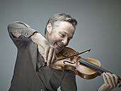 Portrait of smiling man playing violin - RH000302