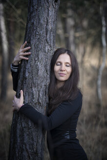 Austria, young woman hugging a tree - MW000007