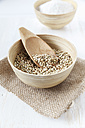 Bowl of buckwheat grains with wooden shovel on jute and white wooden table - EVGF000433