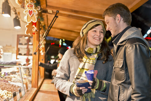 Germany, Berlin, young couple buying sugar roasted almonds at Christmas market - CLPF000062
