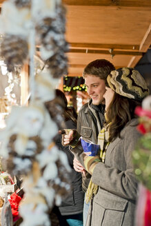 Germany, Berlin, young couple watching offerings at Christmas market - CLPF000059