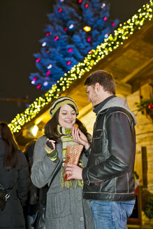 Germany, Berlin, young couple with deep-fried pastries at Christmas market - CLPF000056