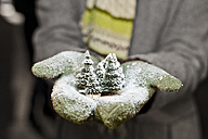 Young woman with gloves holding Christmas decoration, partial view - CLPF000052