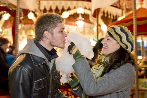 Germany, Berlin, happy young couple with candyfloss at Christmas market - CLPF000050