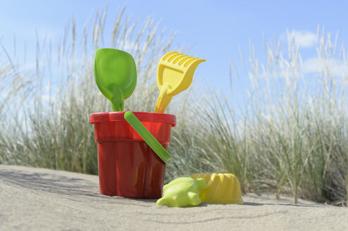 Colourful sandbox toys on sandy beach - CRF002569