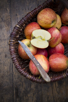 Basket of sliced and whole red apples and kitchen knife on wooden table - LVF000683