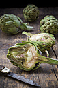 Sliced and whole organic artichokes and kitchen knife on wooden table - LVF000677