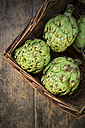 Basket of organic artichokes on wooden table, view from above - LVF000674