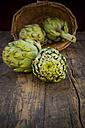 Basket of organic artichokes on wooden table - LVF000672