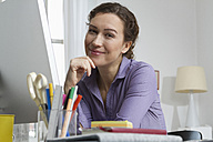 Woman at home sitting at desk with computer - RBYF000331
