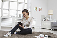 Woman at home reading e-book - RBYF000346