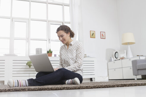 Woman at home using laptop - RBYF000471