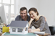 Couple at home with model house - RBYF000373