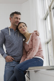 Smiling couple embracing at the window - RBYF000379
