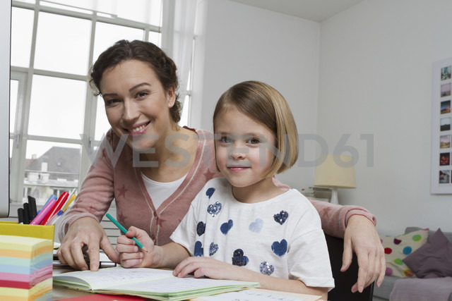 Portrait of mother with daughter at desk - RBYF000398