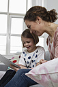 Mother and daughter on couch with tablet computer - RBYF000407