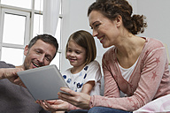 Mother, father and daughter on couch with tablet computer - RBYF000410