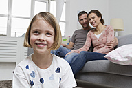 Blond girl in living room with parents in background - RBYF000416