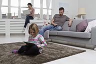 Mother, father and daughter using portable devices in living room - RBYF000425