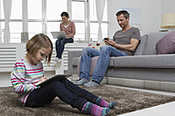 Mother, father and daughter using portable devices in living room - RBYF000483