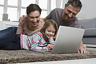 Father, mother and daughter using laptop on carpet in living room - RBYF000464