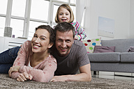 Happy mother, father and daughter lying on carpet in living room - RBYF000490