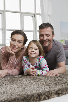 Happy mother, father and daughter lying on carpet in living room - RBYF000493