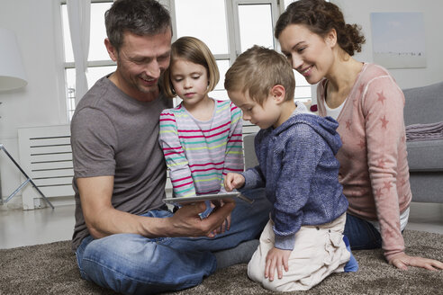 Happy family of four using tablet computer in living room - RBYF000496