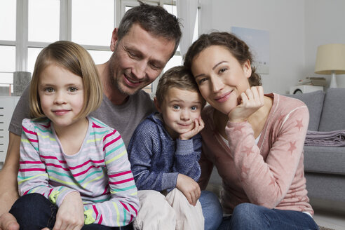 Happy family of four in living room - RBYF000461