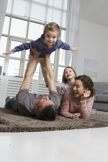 Playful family in living room - RBYF000501