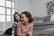 Happy mother and daughter lying on carpet in living room - RBYF000427