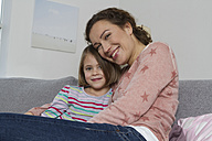 Happy mother and daughter sitting on couch - RBYF000430