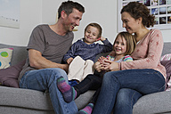 Happy family of four sitting on couch - RBYF000433