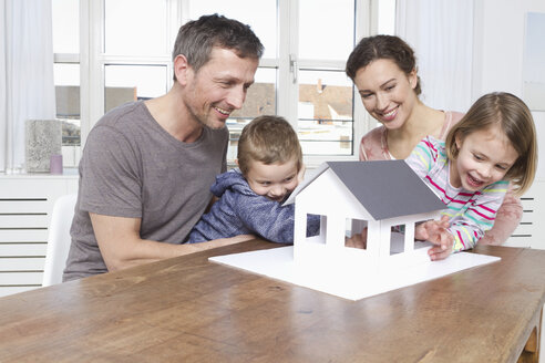 Family of four looking at house model - RBYF000450