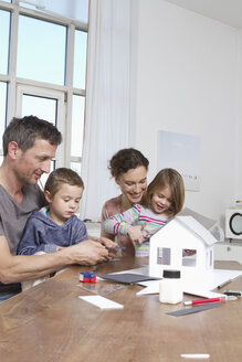 Family of four constructing house model - RBYF000453