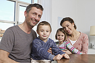 Smiling family of four at home - RBYF000456