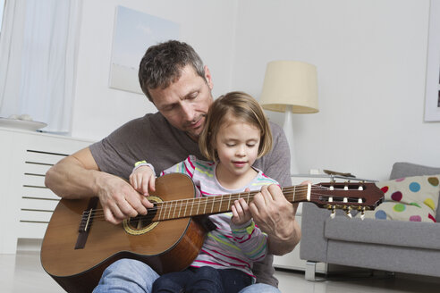 Father teaching daughter to play guitar - RBYF000458