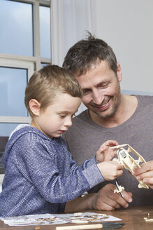 Father and son tinkering model airplane - RBYF000462