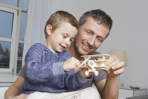 Father and son playing with model airplane - RBYF000463