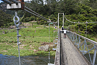 New Zealand, North Island, Waikato, Karangahake Gorge, family crossing suspension bridge - JB000028