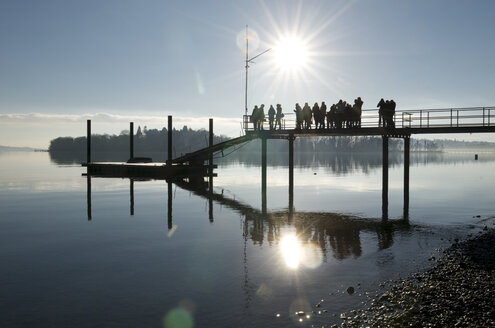 Germany, Baden-Wuerttemberg, Constance District, Lake Constance, Mainau, persons on jetty against the sun - JED000167